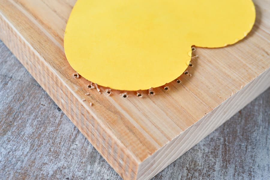 A side view of a cardstock yellow heart on an unfished piece of wood with small drill holes around the outer edge of the heart