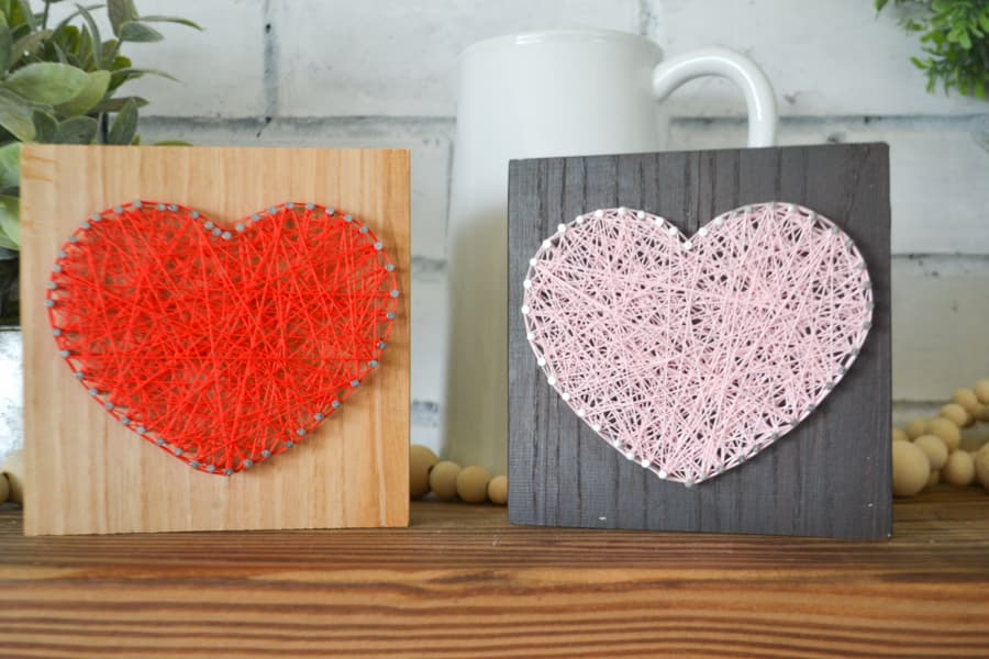 A pink string art heart on a dark brown piece of wood sitting next to a red string art heart on an unfinished piece of wood on a wood mantel