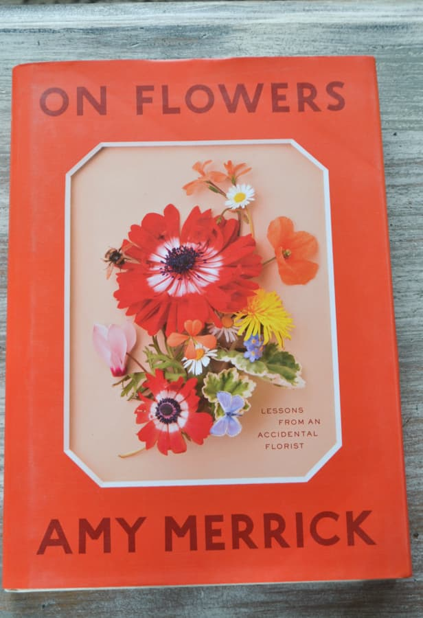 "An above view of an orange book called ""On Flowers"" on a whitewashed table"