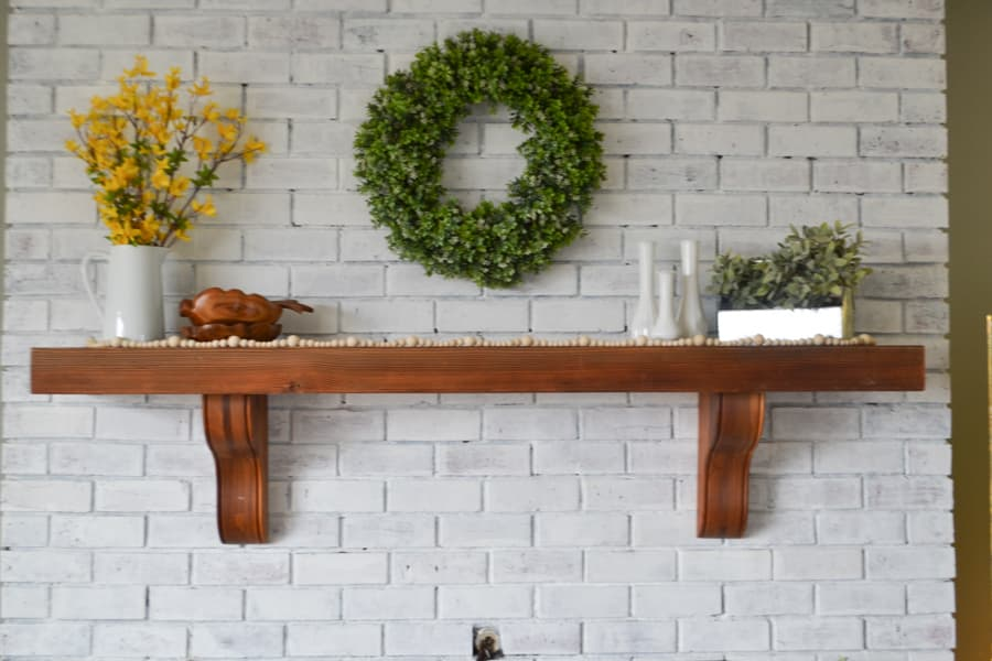 A brown mantel against a white brick fireplace with a white pitcher with yellow forsythia branches and brown wood bowls on the left and a tin container with greenery and white milk glass vase on the right and raw wood beaded garland laying across the entire mantel length
