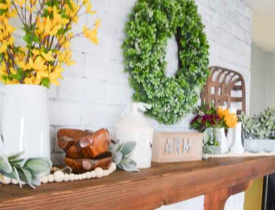 A close up of a brown mantel against a white brick fireplace with a green boxwood wreath and multiple arrangments