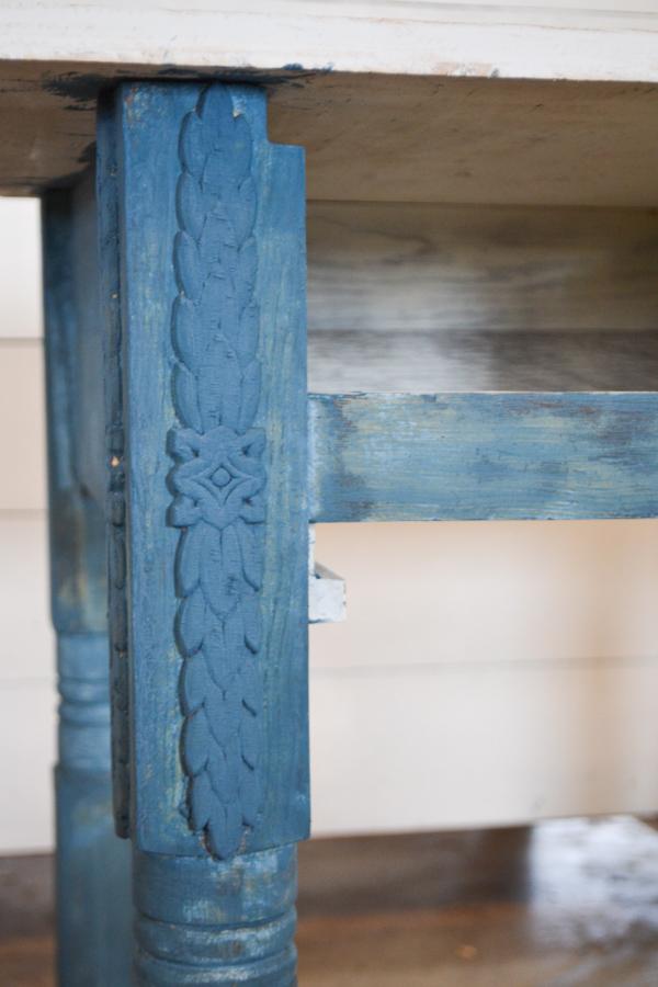 A close up picure of a blue painted wood applique