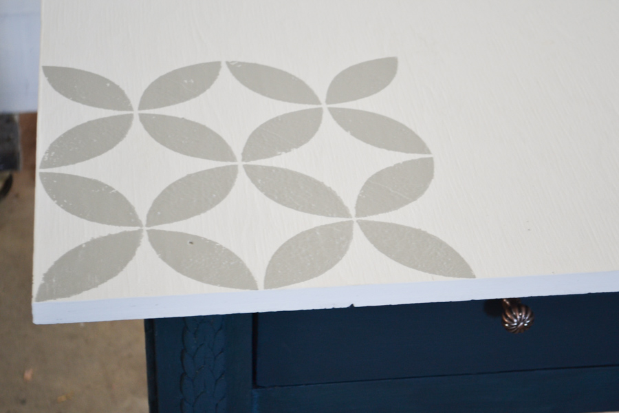 A close up of a gray flower pattern on top of a white table