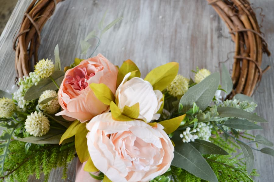 Pink peonies surrounded by greenery on each side being held up by a hand on a grapevine wreath laying on a whitewashed table