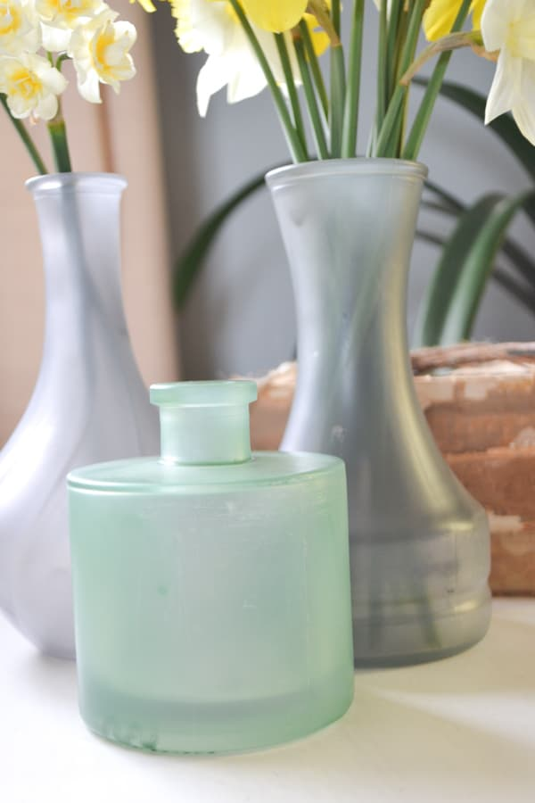 A close up of three bud vases, two gray ones in the back and a pale green in the front sitting on a white table