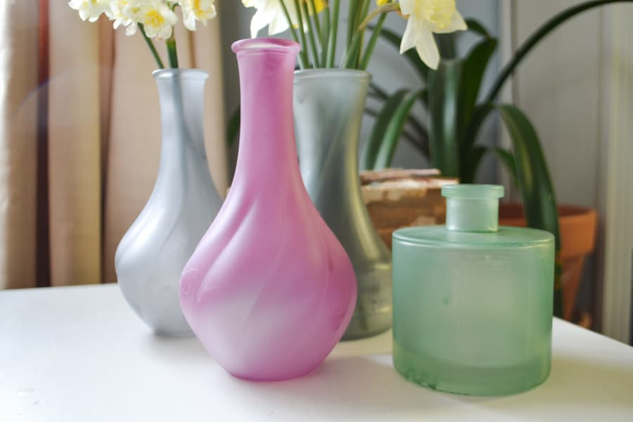 A close up of four sea glass spray painted bud vases, two gray in the background and a pink and green in the foreground with daffodils in the vases