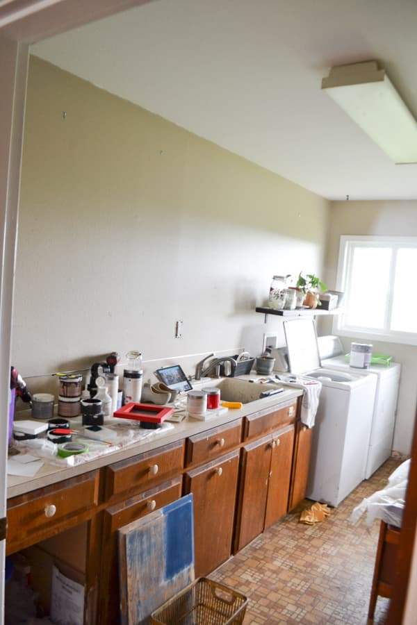 A view of a laundry room with a bank of brown cabinets and a brown wall with a white ceiling and a long flourescent light in the center