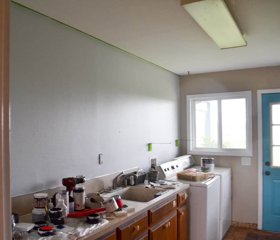 A laundry room wall painted a light gray with a white ceiling and a flourescent light above and brown cabinets