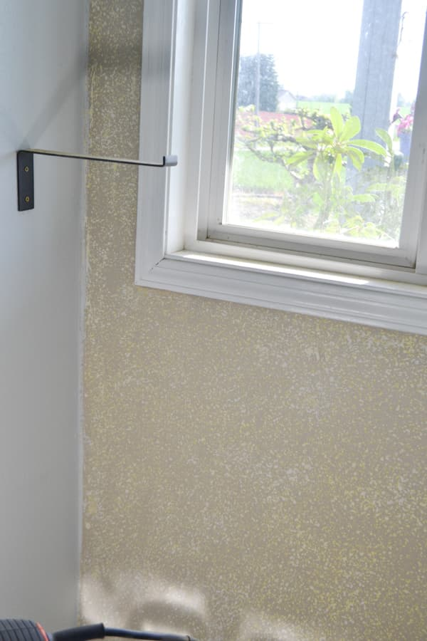 A close up of a sanded textured wall below a window