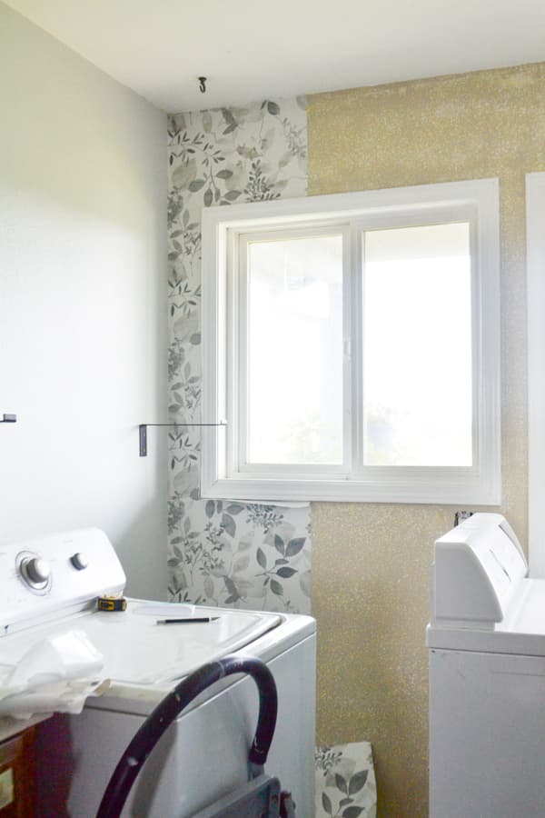 A wall with a window and one strip of wallpaper installed around the window
