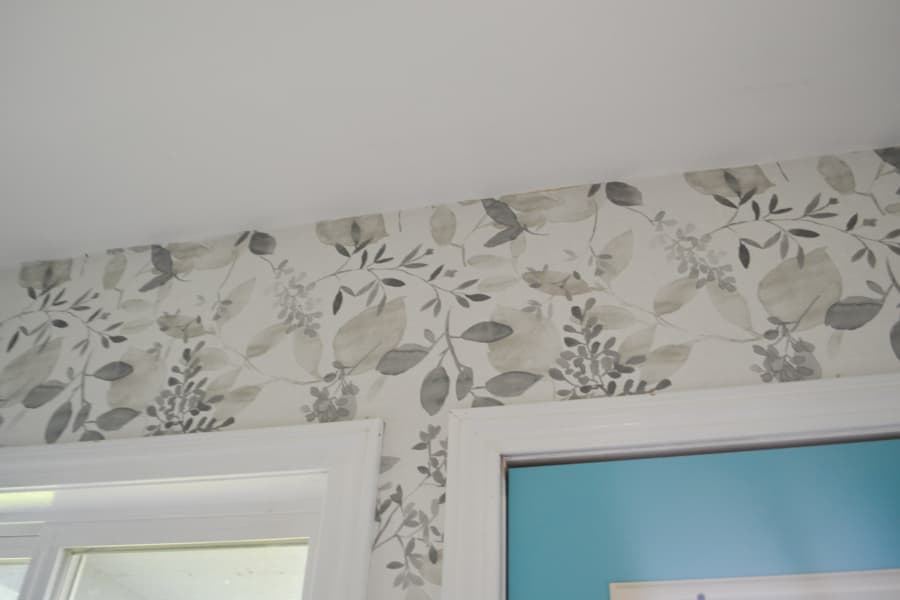 A close up of a grey floral peel and stick wallpaper on a wall above a window and door