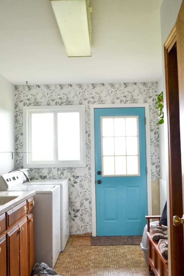 A grey floral wallpaper on a wall with a window and a blue door on the wall, a brown floor and brown cabinets and a flourescent light above