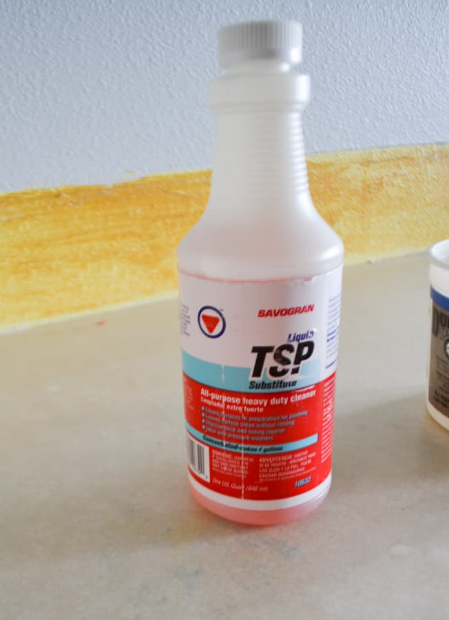 A close up of a TSP substitute bottle sitting on a laminate counter with a bright yellow glue background