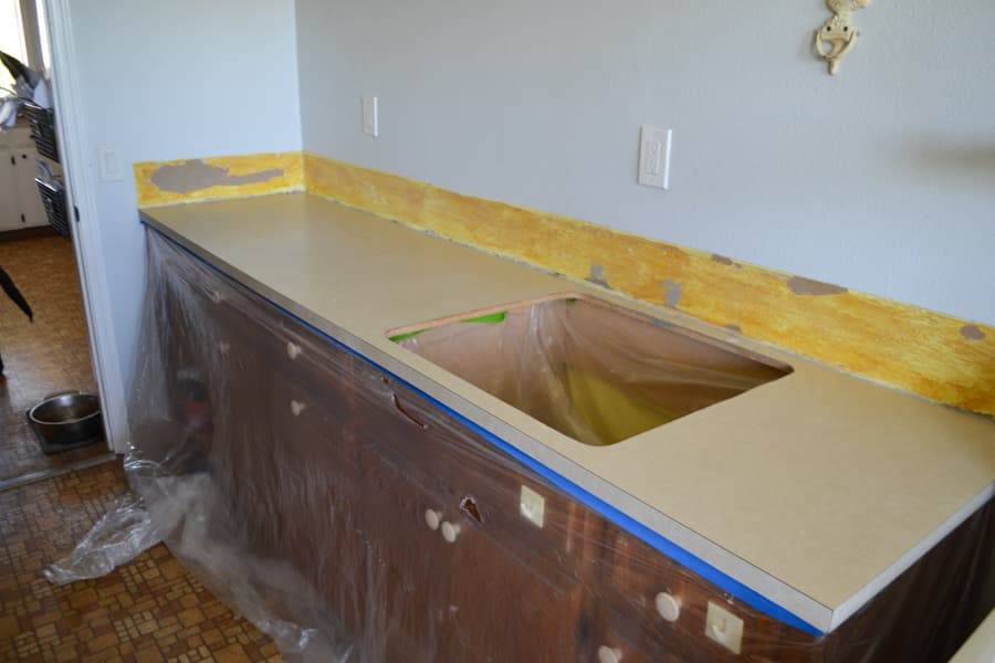 A laminate countertop laundry room with brown cabinets and yellow glue residue around the border