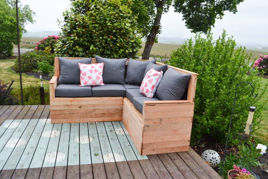 """An """"L"""" shaped all wood sectional with grey cushions and watermelon pillow sitting on a deck with a painted rug"""
