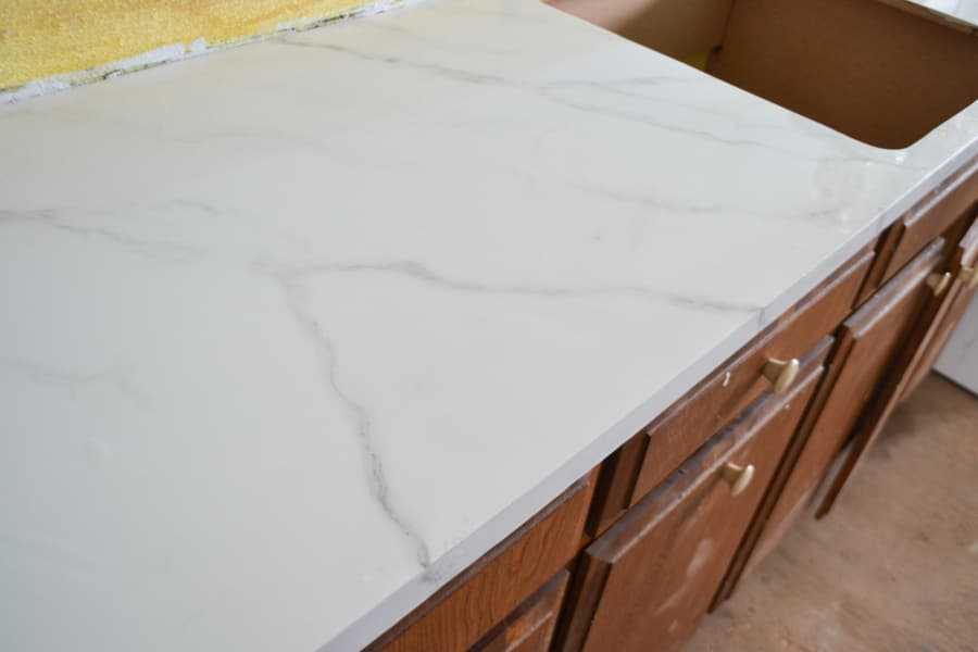 a close up of a marble looking painted countertop on brown cabinets