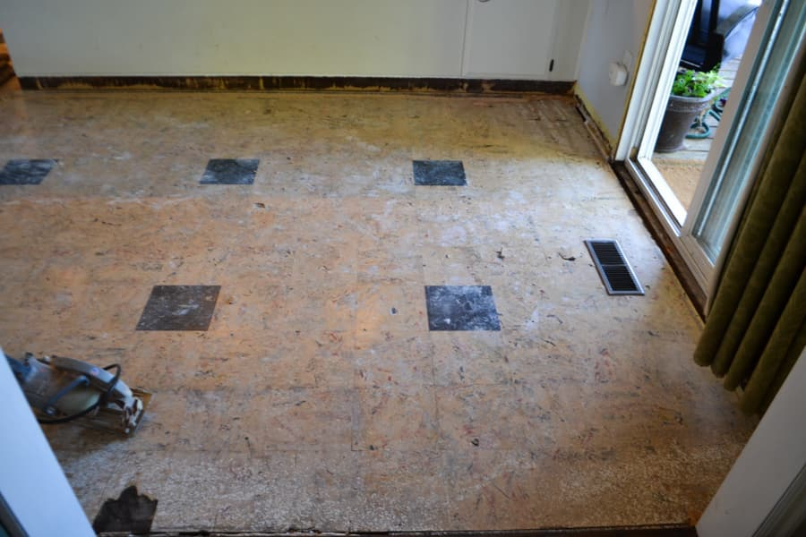 A look down at an off yellow/cream linoleum tile floor with dark green tiles with a heat vent to the right and a sliding door to the right of the heat vent