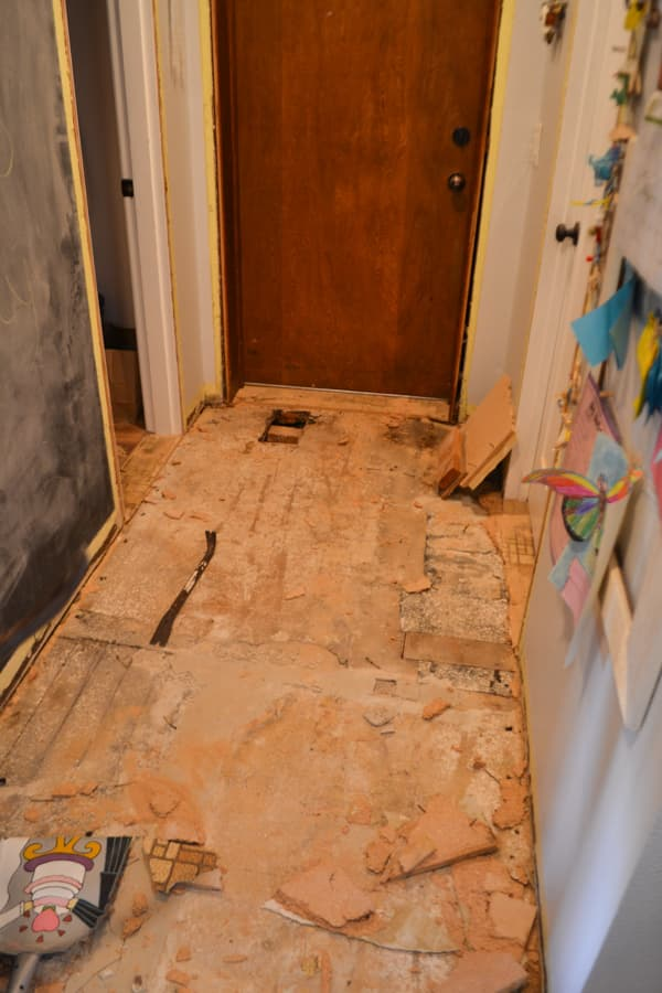 A hallway flooring that is torn up with a brown door and a hole in the floor in front of the brown door