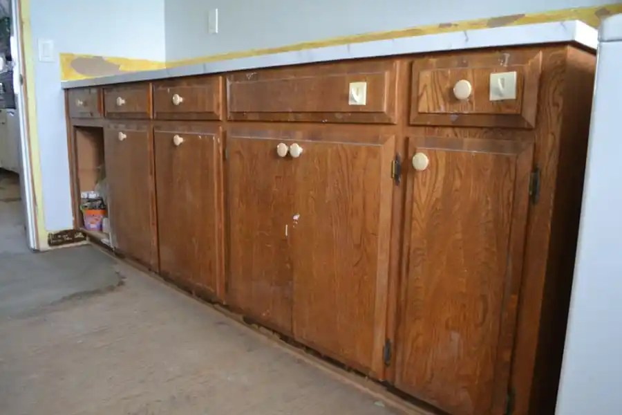 A close up of brown cabinets with off white knobs