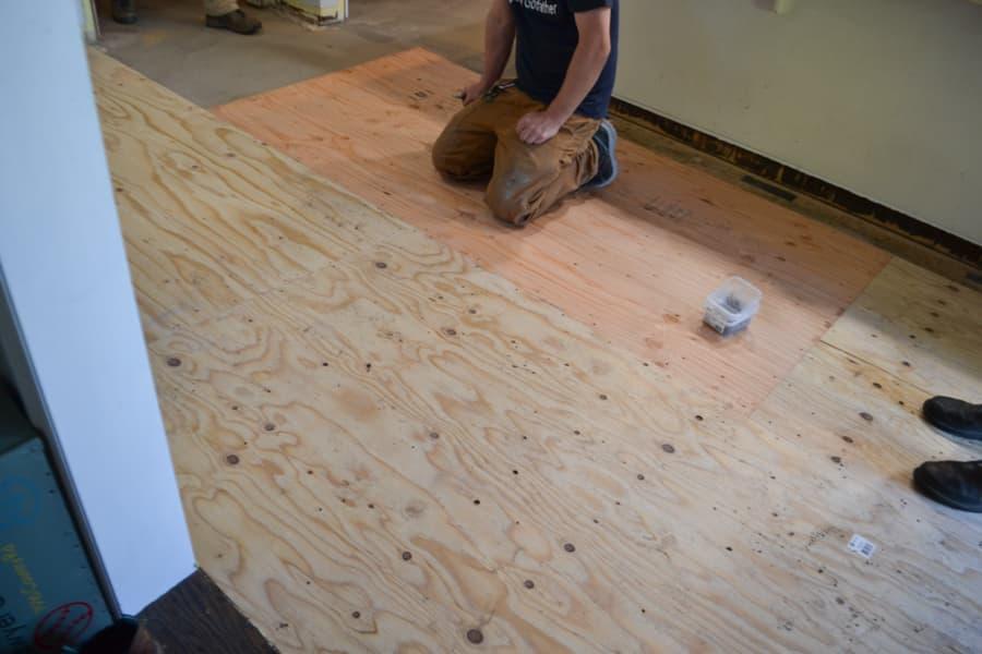 A man kneeling on a plywood subfloor
