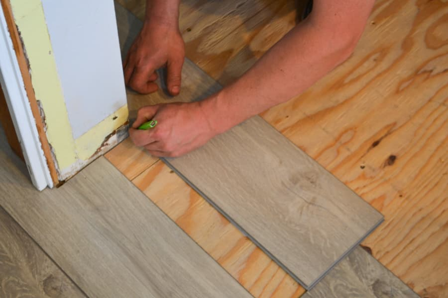 A close up of a man's hands marking a piece of gray vinyl flooring with a pencil against a plywood floor