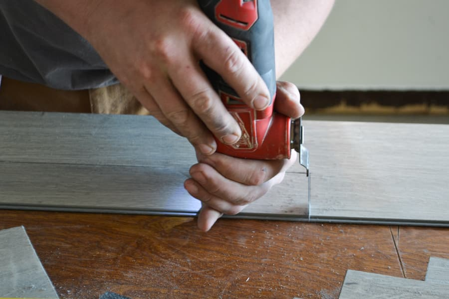 A close up of a man's hand using a red multi-tool to cut vinyl plank flooring