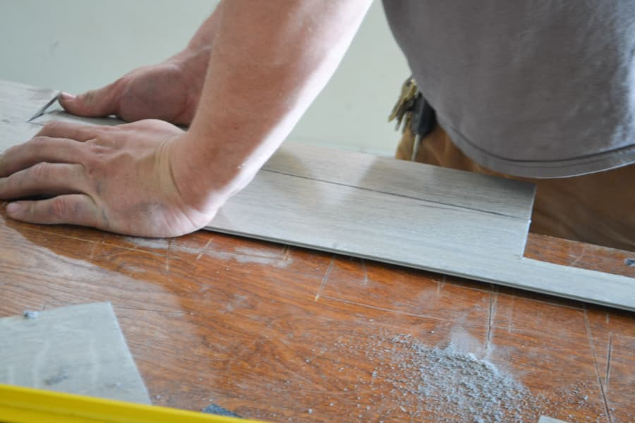 A man's hand holding a vinyl flooring piece with one hand and bending it at the score line with the other