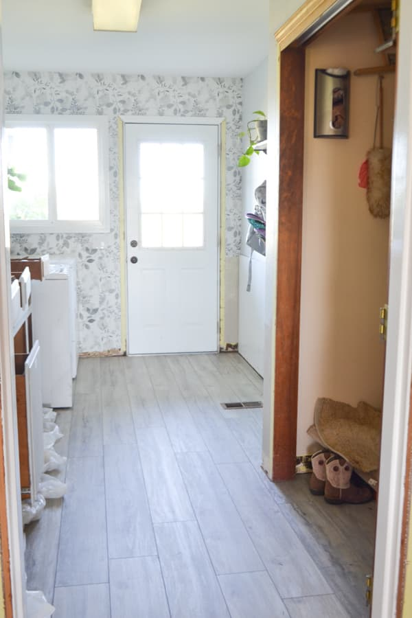 A laundry room with a white door with a window and a window to the left with a floral wallpaper and a grey floor