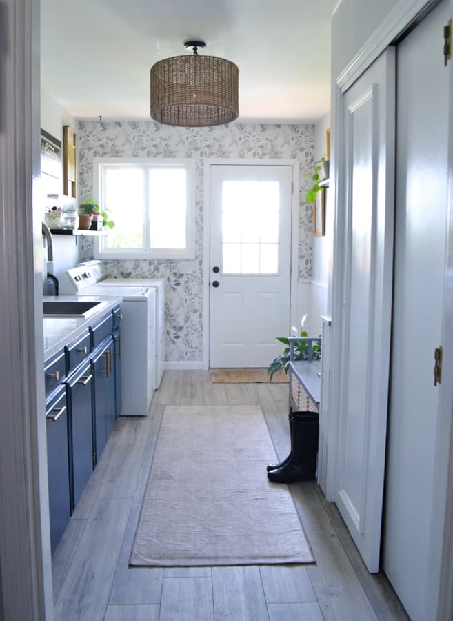 A full room view of a laundry room with blue cabinets, wallpaper on the far wall, a rug down the center and white closet to the right