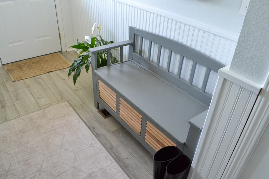 Looking down at a grey shoe bench with raw wood insets and a runner rug and a rug near the door with a plant next to the bench
