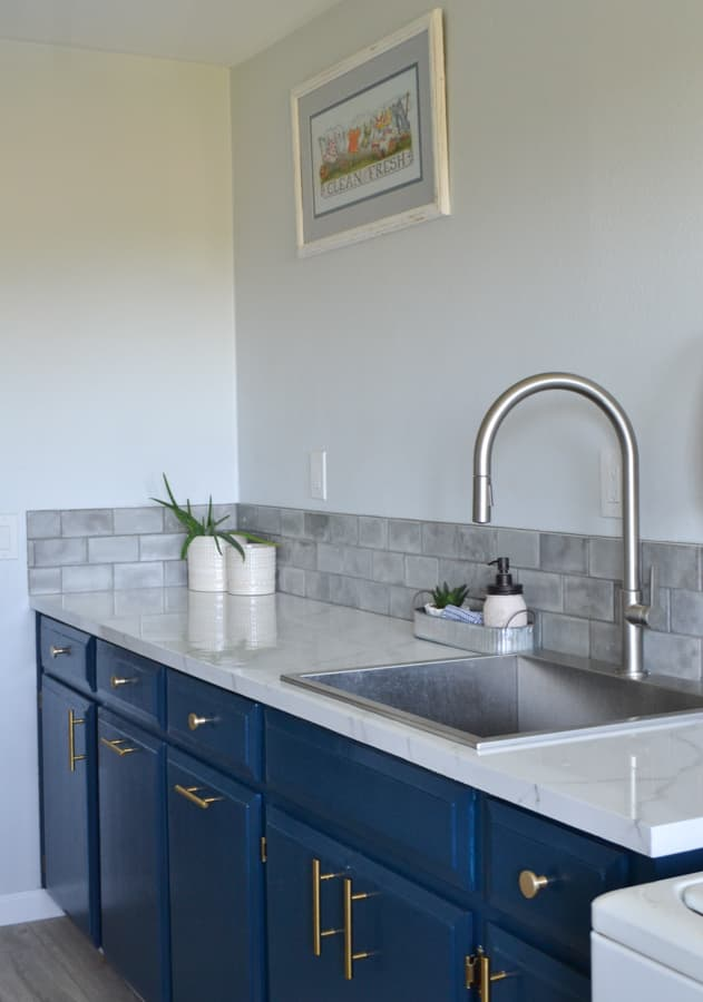 Blue cabinets with a stainless steal faucet and sink with a marble counter