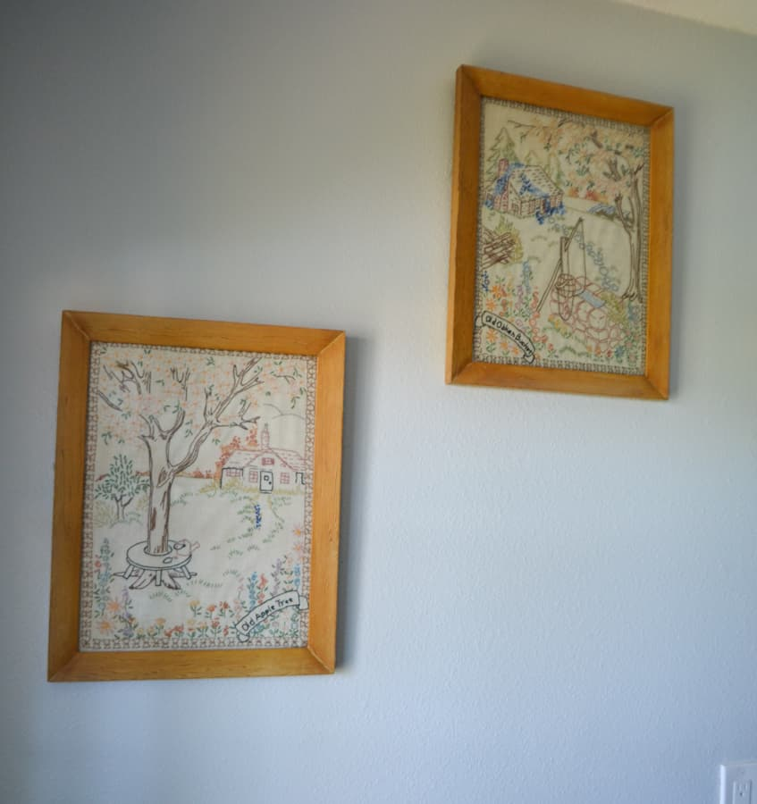 A close up view of two embroidery designs that have been framed in a natural frame hung next to each other