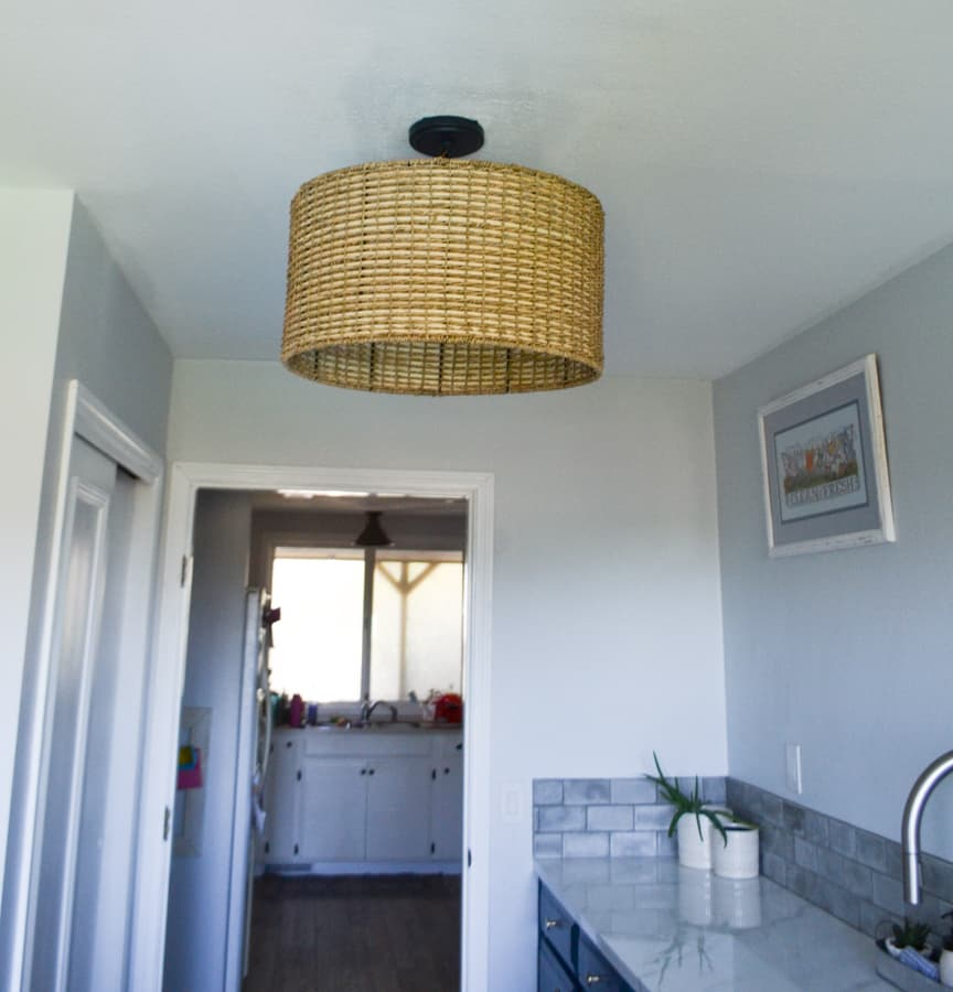 A view to a ceiling in a laundry room with a marble countertop cabinet to the right and a white closet to the left