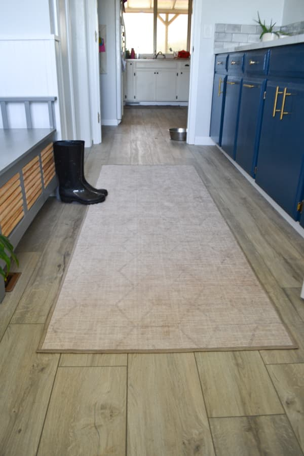 A view of a runner rug on the floor of a laundry room with a bench and black rain boots to the left and blue cabinets to the right