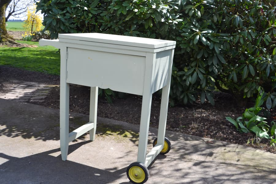 A flip top sewing table sitting outside with a green bush behind