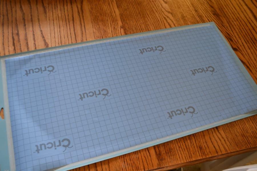 An above view of blue Cricut stencil vinyl on a cutting mat