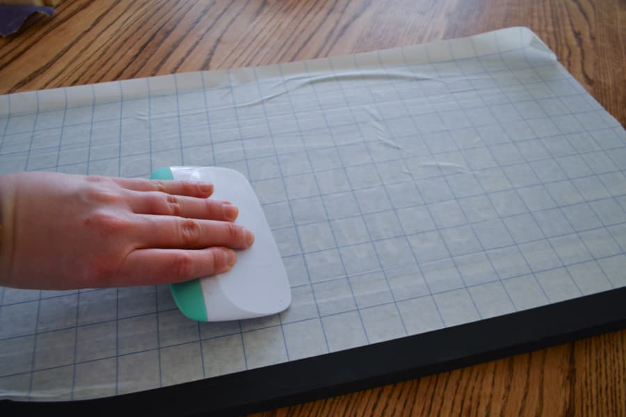 An above view of a hand hold a scraper over a gridded transfer sheet