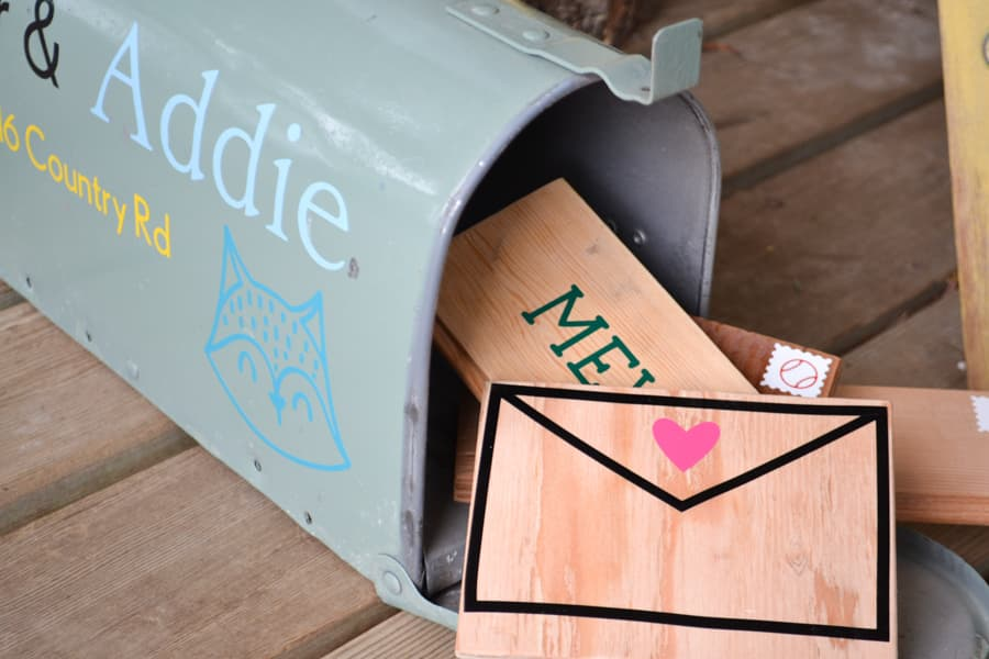A close up of scrap wood pieces with an envelope design on them spilling out of a spray painted mailbox