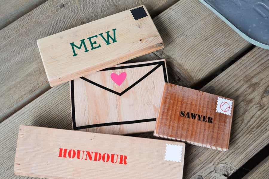 A close up of scrap wood pieces cut and with vinyl on them to look like pieces of mail