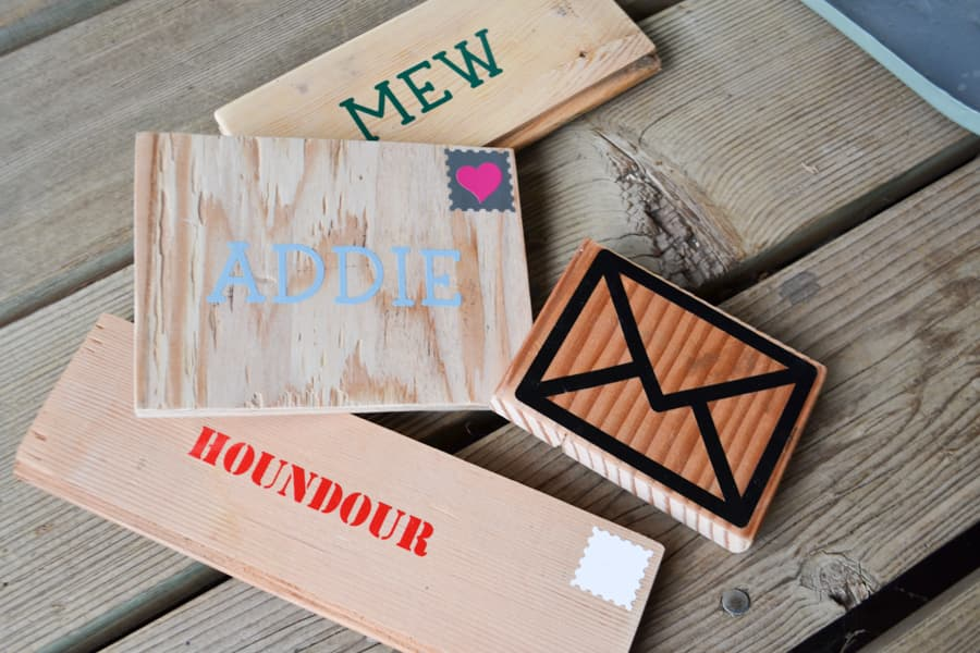 A close up of four scrap wood pieces with outdoor vinyl to look like envelopes
