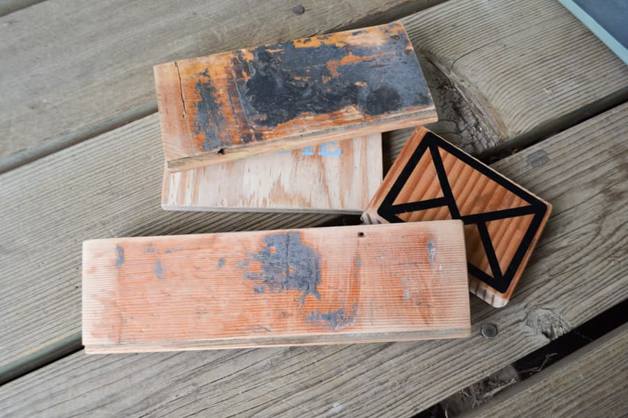 A close up of four scrap wood pieces with the backs showing black mastic still stuck on