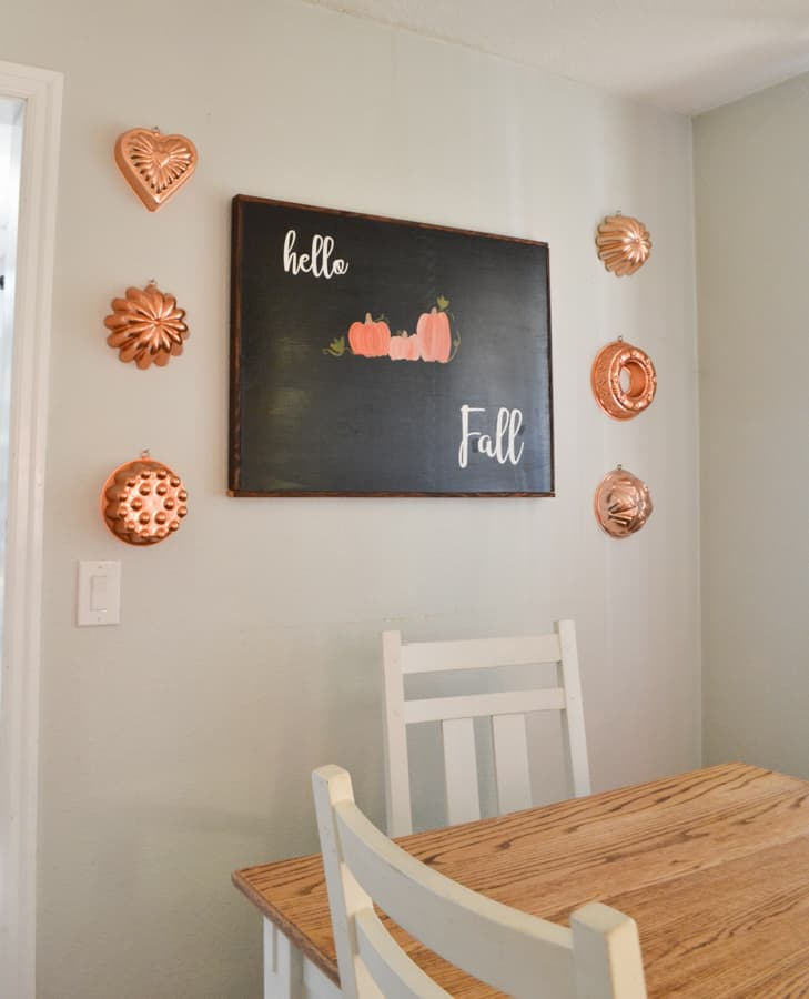 """A black sign with the white wording stating """"hello Fall"""" with orange pumpkins painted in the center and copper molds hung on each side of the sign on the wall"""