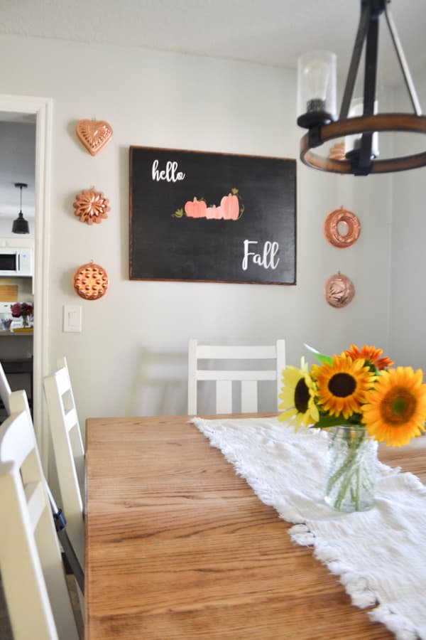 A view of a black hello fall sign hung on a wall in a dining room with sunflowers sitting on a white runner on the table