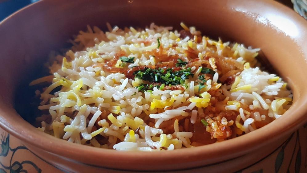 Lamb biryani served in a pot includes rice, meat, cinnamon, cardamom, saffron, coriander.