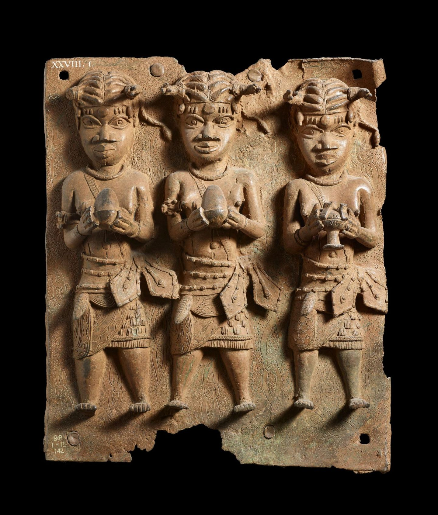 Benin bronze plaque at the British Museum London showing three figures holding bowls of food