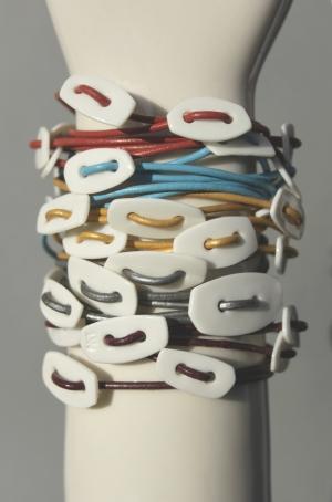 Hvide porcelænsler monteret på farvet lædersnor