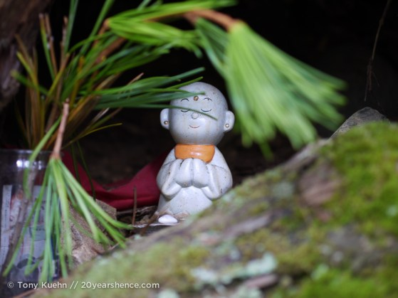 A little figurine nestled in a tree