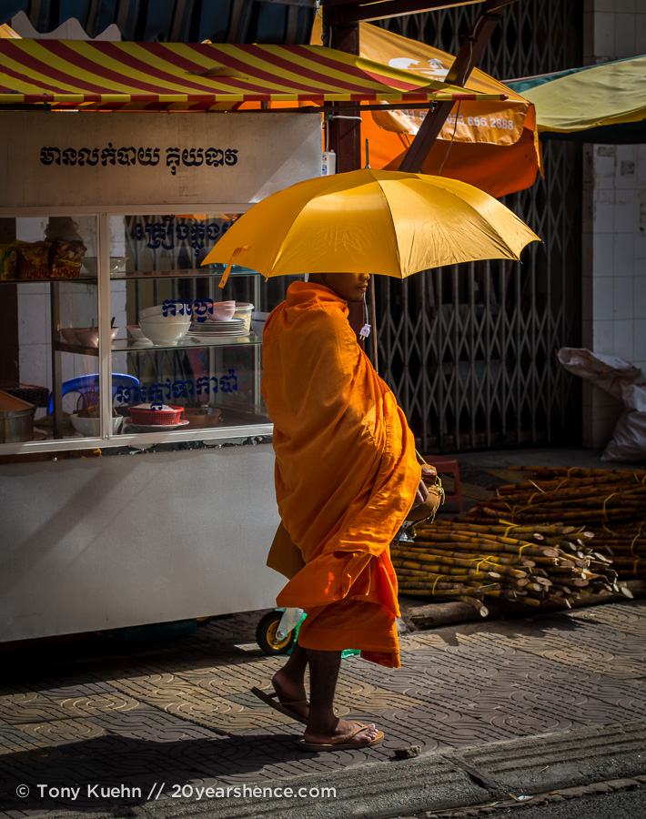 Cambodian monk with a yellow umbrella in Phnom Penh