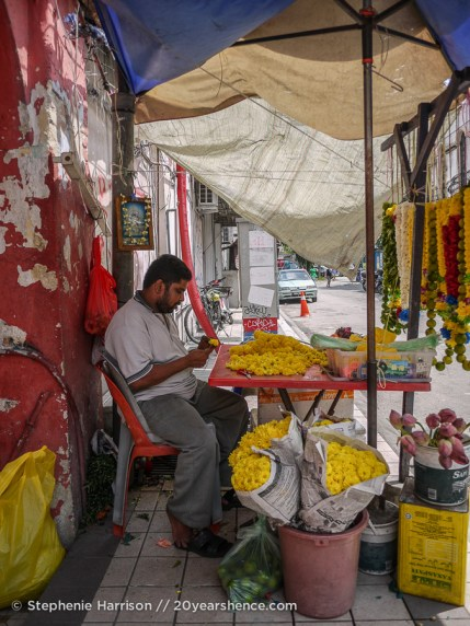 Man making Hindu flower garlands