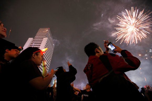 People watch as fireworks explode around the Selamat Datang Monument during New Year's Eve celebrations in Jakarta